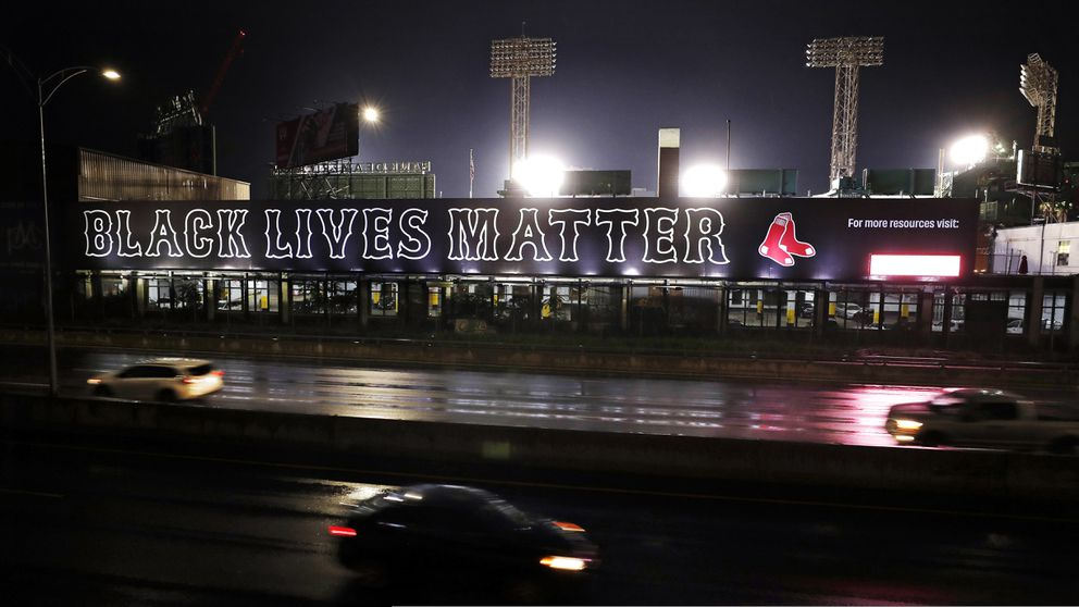 Cars along the Massachusetts Turnpike drive past a giant 'Black Lives Matter ' mural, Wednesday evening, July 22, 2020, outside Fenway Park, at the rear, in Boston. (AP Photo/Charles Krupa)