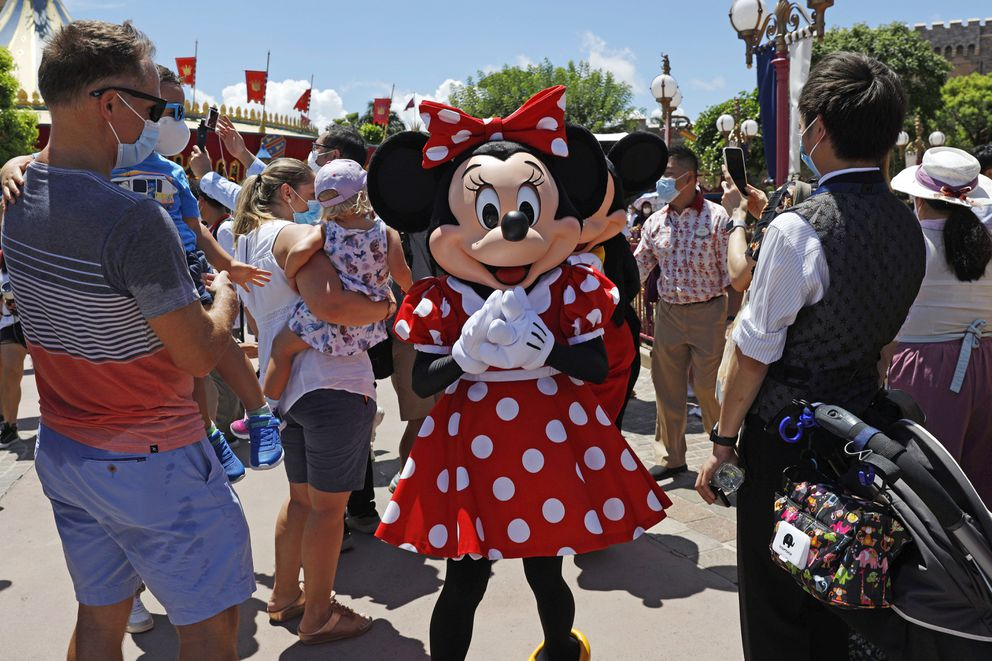 The iconic cartoon character Minnie Mouse reacts to visitors at the Hong Kong Disneyland Thursday, June 18, 2020. In March, Hong Kong closed its borders to overseas countries, restricting visitors to those who have spent more than 14 days in mainland China, Macao and Taiwan. Tourist numbers plunged nearly 90%, with only about 3.5 million visitors arriving in the city between January and June this year. The city's airlines, hospitality and tourist industries – which had already took a hit from months of anti-government protests last year – took a second beating, with the government pledging $51.6 million in subsidies to help them stay afloat. (AP Photo/Kin Cheung)