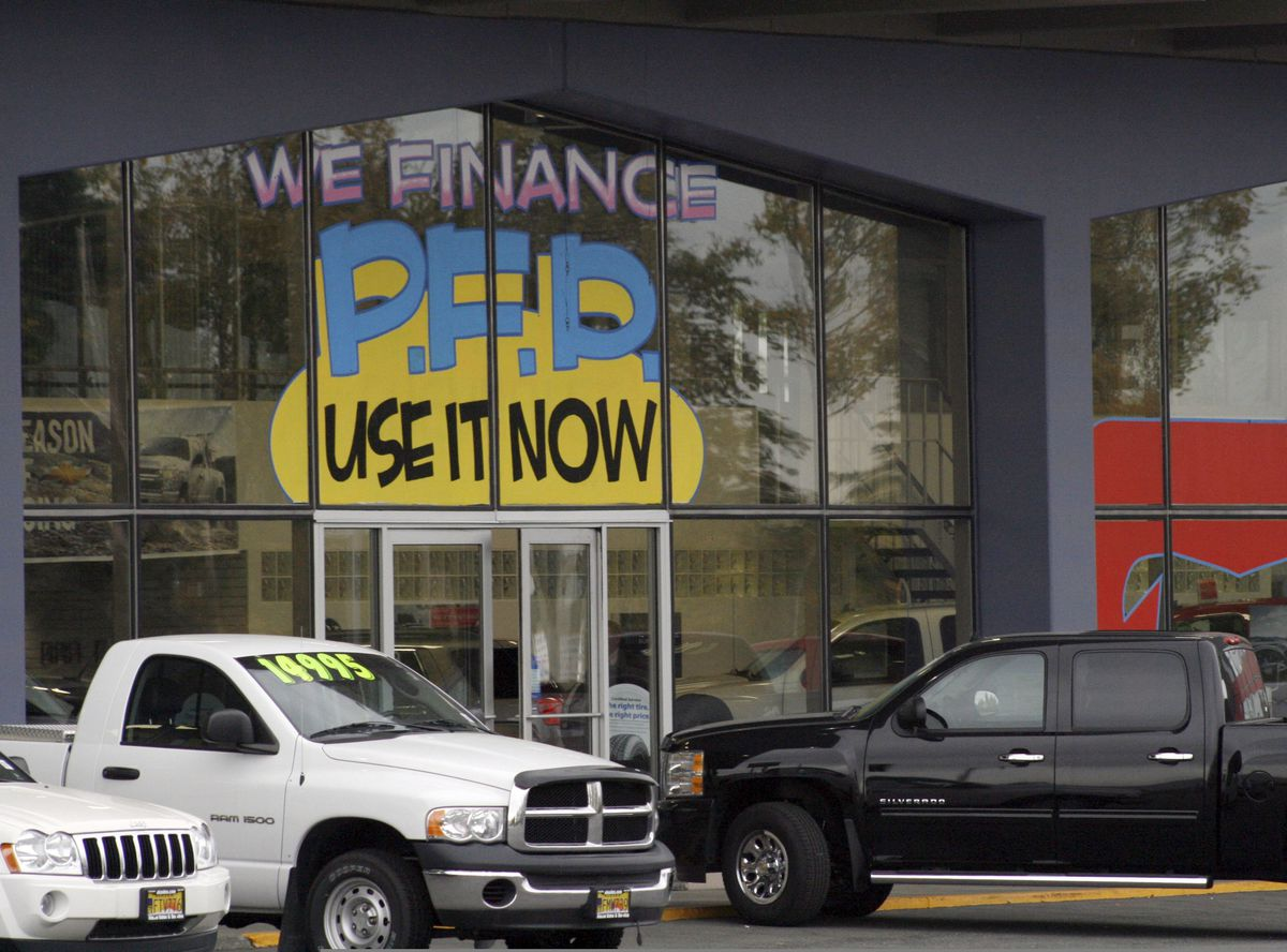 FILE - In this Monday, Sept. 19, 2011 file photo, an auto dealership in Anchorage, Alaska, advertises PFD, or Permanent Fund Dividend, sales. (Mark Thiessen / AP archive 2011)