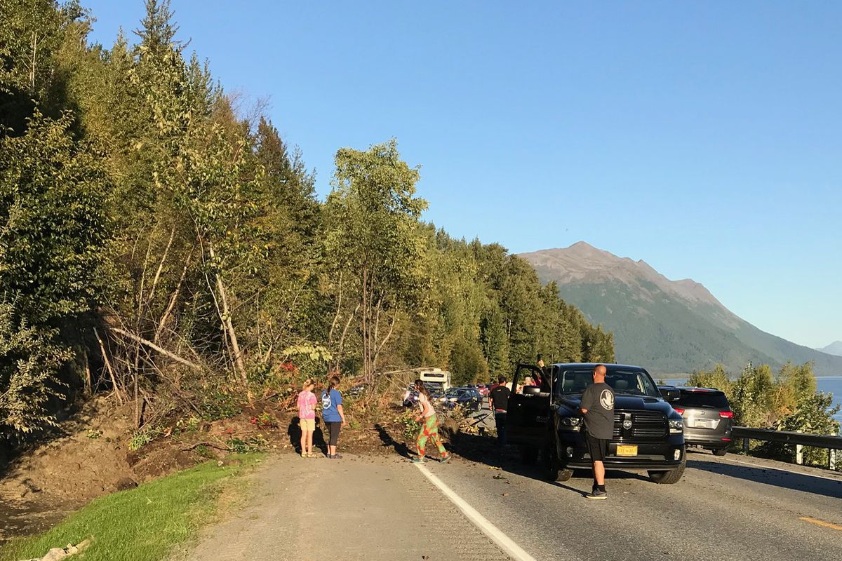 People helped move dirt, rocks and trees and directed traffic after a landslide crossed the northbound lane of the Seward Highway at Mile 105 on Saturday evening, Sept. 8, 2018. (Photo by Kim Sayers-Fay)