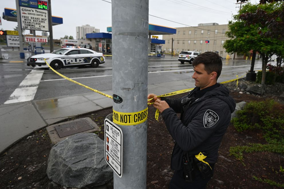 Officer Wallace moves crime scene tape closer to Fifth Avenue as Anchorage Police investigate the scene of an early morning fatal shooting along Gambell Street near downtown Anchorage on Saturday, June 19, 2021. (Bill Roth / ADN)
