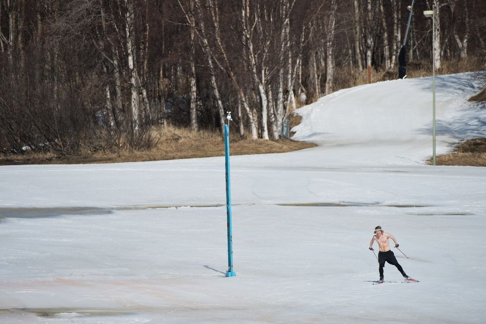 Mark Chase makes the most of both the warm, sunny weather and the snow that remains in the Kincaid Park stadium by skiing with no shirt on April 16, 2018. Chase said he's training for a trail race this summer (Marc Lester / ADN)