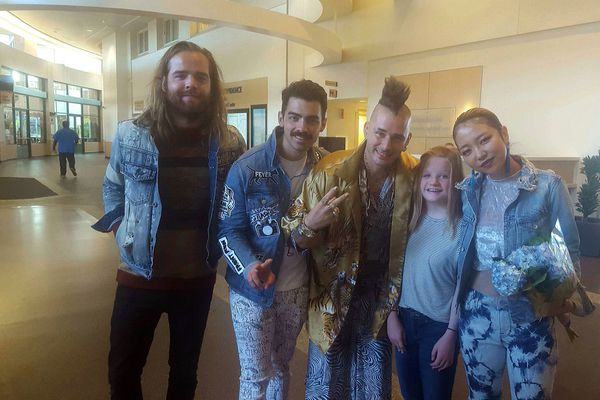 Ashley Perry, of Anchorage, stands with the members of the pop-rock band DNCE, including its lead singer Joe Jonas (second from left), at the Providence Alaska Medical Center on Monday, Sept. 4. (Kimberly Perry)