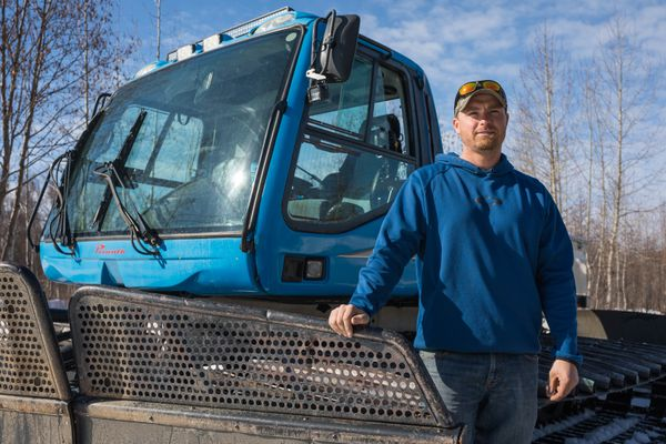 Bryce Dean, one of the owners of Willow Creek Resort, stands next to a snowcat that he plans to use for ski operations in Hatcher Pass next winter, on Wednesday, April 10, 2019. (Loren Holmes / ADN)