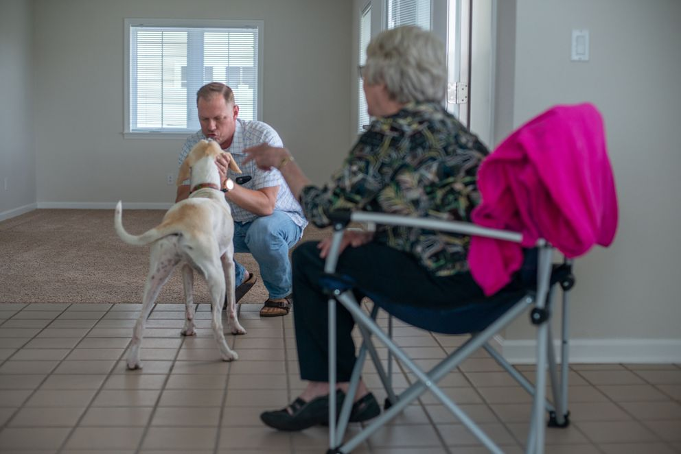 Lt. Col. Stephen Meister plays with his dog, Charlie, while his mother, Betty Matthiessen, talks about his new assignment in early July. His quarters were bare because his belongings had not arrived. Photo by Lido Vizzutti For The Washington Post