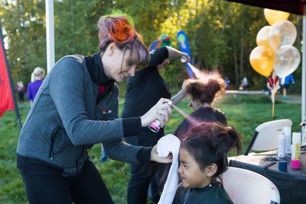 Sasha McCole with Sport Clips gives Lucy Abad, 6, a colorful hairdo. (Loren Holmes / ADN)