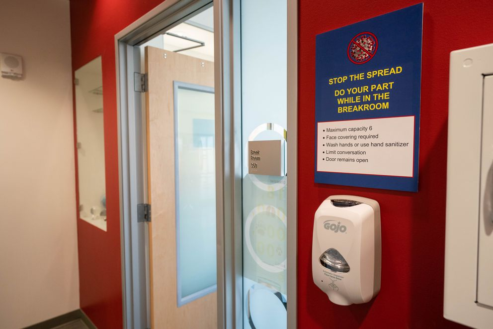 A sign outside a break room reminds employees to take precautions to prevent the spread of COVID-19 at Alyeska Pipeline Service Company on Thursday, May 14, 2020 in Anchorage. (Loren Holmes / ADN)