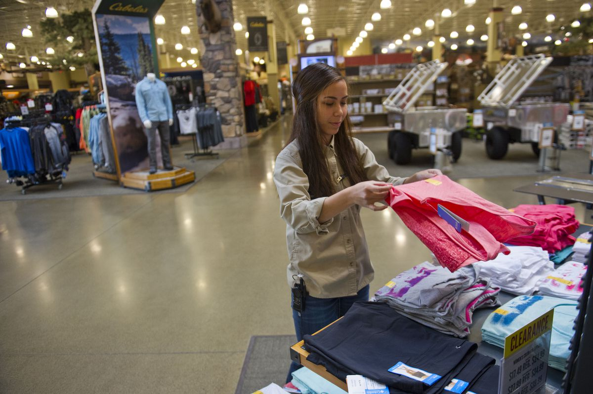 Monica Mojica folds clothes for a display in the Cabela's store in South Anchorage on Friday, July 15, 2016. (Marc Lester / Alaska Dispatch News)