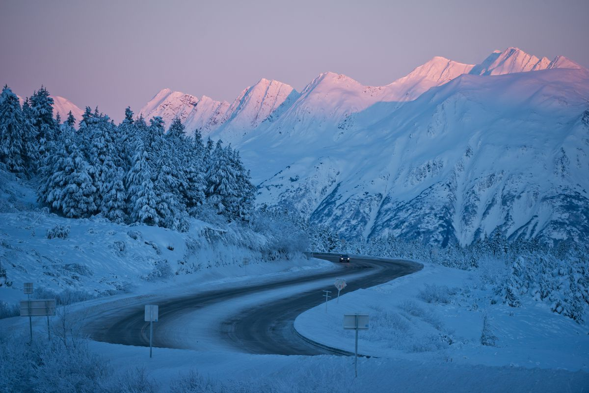 Peaks near Turnagain Pass catch the last bit of afternoon sunlight as a car heads southbound on the Seward Highway on Thursday, December 22, 2016. (Marc Lester / ADN)