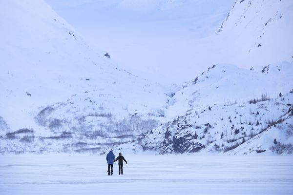Poonyanuch Klobuczek, right, and Heinrich Klobuczek walk on the ice of Portage Lake on Feb. 22, 2021. On Wednesday, March 17, an out-of-state visitor reported that he fell through the ice at Portage Lake but managed to pull himself out. (Emily Mesner / ADN archive)