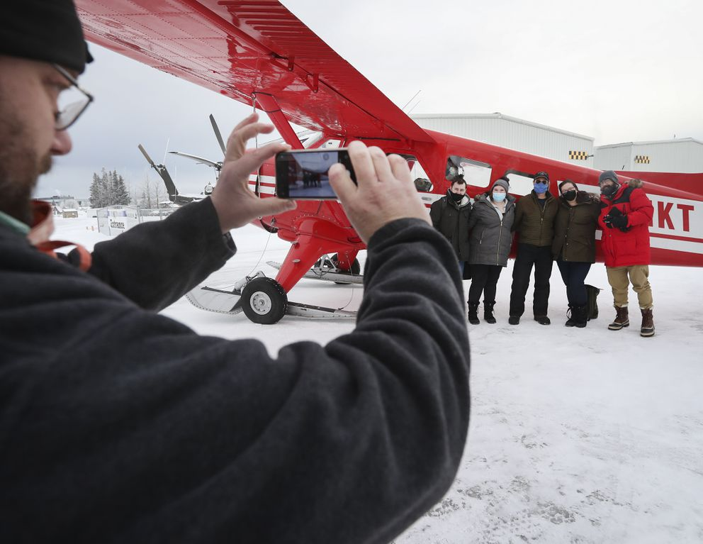 Willis Thayer takes a photograph for tourists Nick Holmes, Savannah Reed, Sara Anders and Shaun Grenan, with pilot Scott Rockey, center, after landing at Lake Hood Seaplane Base in Anchorage on Friday, Feb. 5, 2021. (Emily Mesner / ADN)