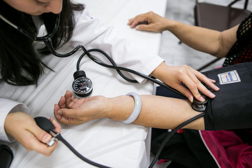 Ei Yupar Win, left, measures a patient's blood pressure during the general medical screening area during the Hsi Lai Temple Health Fair, in Hacienda Heights, Calif., on May 10, 2015. (Marcus Yam / Los Angeles Times / TNS)