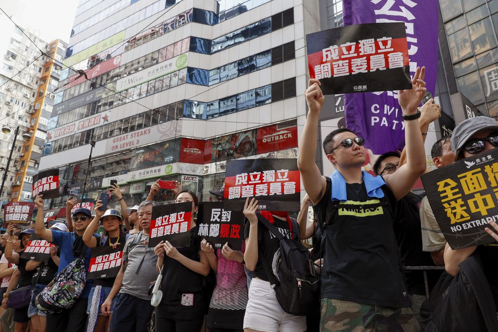 Protesters hold placards reads 'Form an independent investigation on legislative ' as they take part in a march in Hong Kong, Sunday, July 21, 2019. Thousands of Hong Kong protesters marched from a public park to call for an independent investigation into police tactics. (AP Photo/Vincent Yu)
