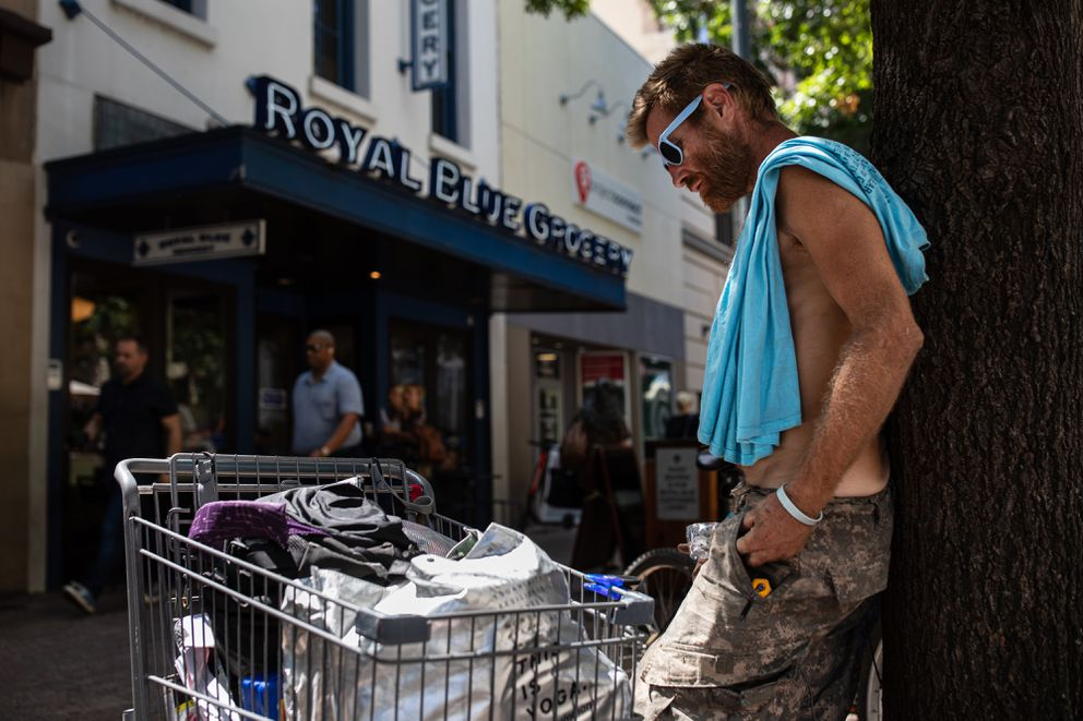 Christopher Paul, who is homeless, stands outside the grocery. Photo by Tamir Kalifa for The Washington Post.