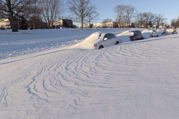 Wind-blown snow buried vehicles in Parkville, Md. Millions of Americans were preparing to dig themselves out Sunday after a mammoth blizzard with hurricane-force winds and record-setting snowfall brought much of the East Coast to a standstill.