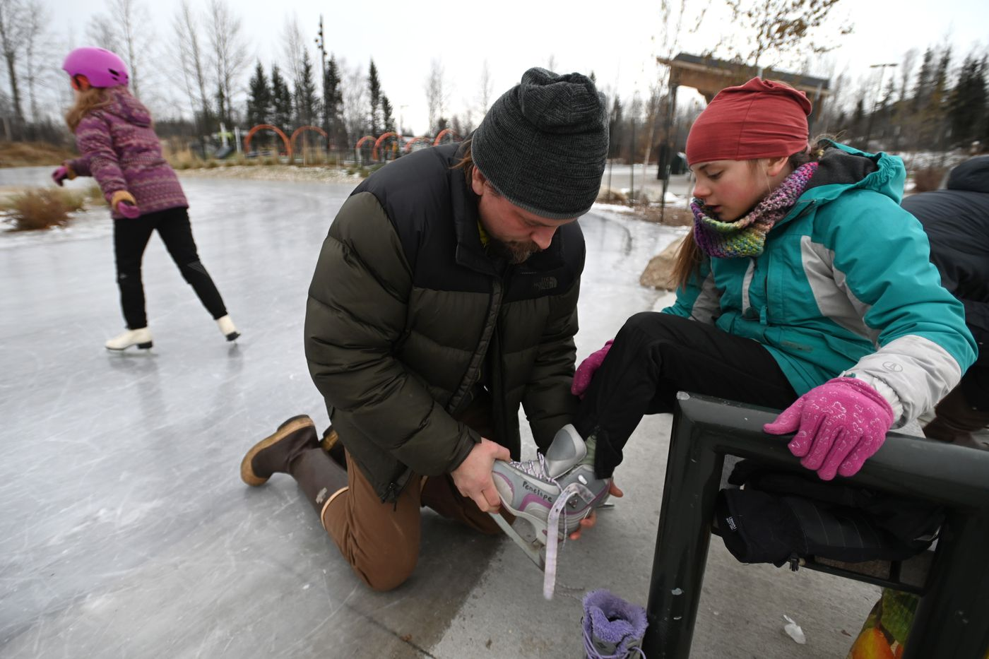 Jeremy Allen helps lace up ice skates for his daughter Penelope, 10, as her sister Isla, 8, skates on the freshly hot mopped ice surface at Chanshtnu Muldoon Park on Thursday, Nov. 5, 2020. (Bill Roth / ADN)