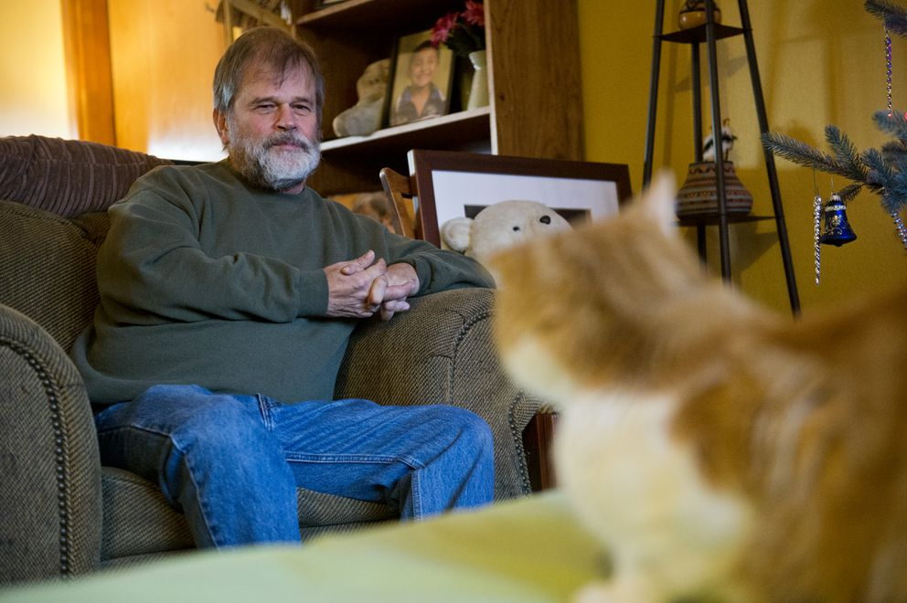Bill Hess looks at his cat Carrizo at his Wasilla home on December 10, 2019. (Marc Lester / ADN)