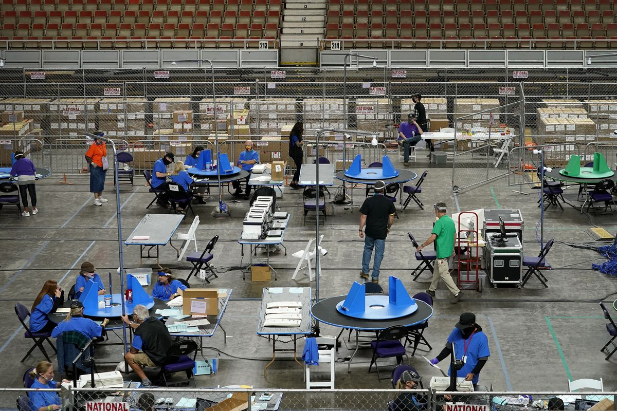 Maricopa County ballots cast in the 2020 general election are examined and recounted by contractors working for Florida-based company, Cyber Ninjas, Thursday, May 6, 2021 at Veterans Memorial Coliseum in Phoenix. The audit, ordered by the Arizona Senate, has the U.S. Department of Justice saying it is concerned about ballot security and potential voter intimidation arising from the unprecedented private recount of the 2020 presidential election results. (AP Photo/Matt York, Pool)