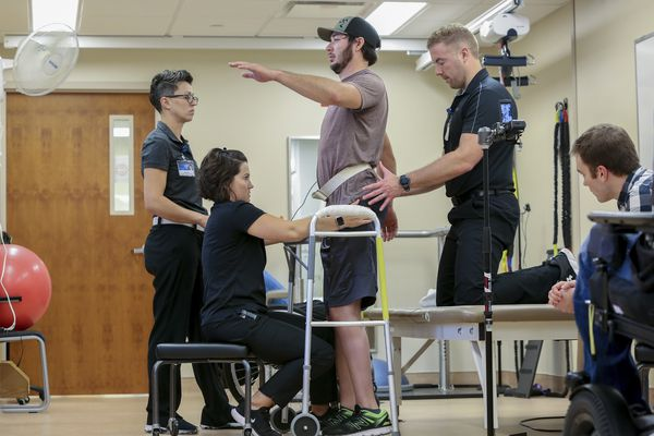 Jered Chinnock stands with the assistance of his therapy team at the Mayo Clinic in Rochester, Minn., on Sept. 18, 2018. Chinnock, paralyzed since 2013, can stand and take steps again thanks to an electrical implant that zaps his injured spine and months of intense rehab as part of a medical study at the clinic. From left are Margaux Linde, Megan Gill, Chinnock, Daniel Veith and Jonathan Calvert. (AP Photo/Teresa Crawford)