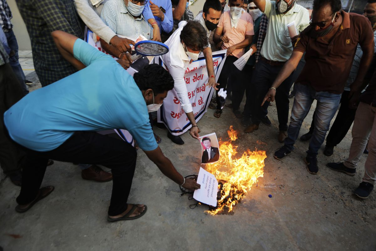 An Indian man burns a photograph of Chinese president Xi Jinping during a protest against China in Ahmedabad, India, Tuesday, June 16, 2020. At least 20 Indian soldiers, including a senior army officer, were killed in a confrontation with Chinese troops along their disputed border high in the Himalayas where thousands of soldiers on both sides have been facing off for over a month, the Indian army said Tuesday. (AP Photo/Ajit Solanki)