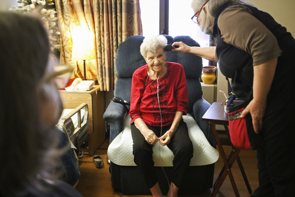 Kim Kiml brushes her mother's hair while she and her sister, Winter Wolf, visit her at the Pioneer Home in Anchorage on Wednesday, Feb. 3, 2021. Their mother, Ellie Brimanis, hasn't been allowed to have visitors since mid-March of last year due to pandemic restrictions. (Emily Mesner / ADN)