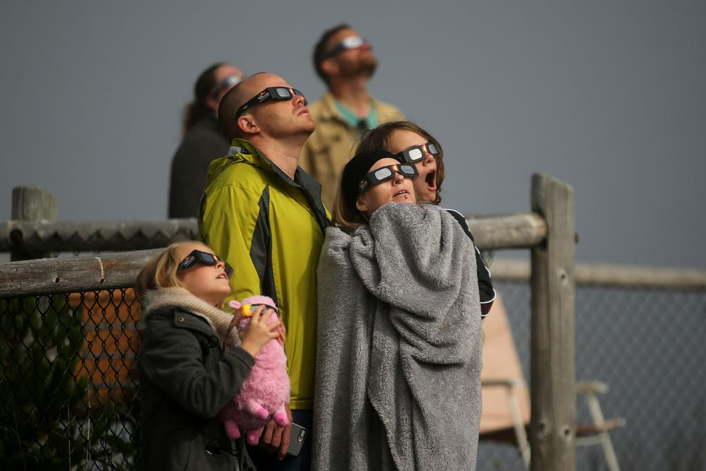People watch eclipse in Depoe Bay, Oregon. REUTERS/Mike Blake