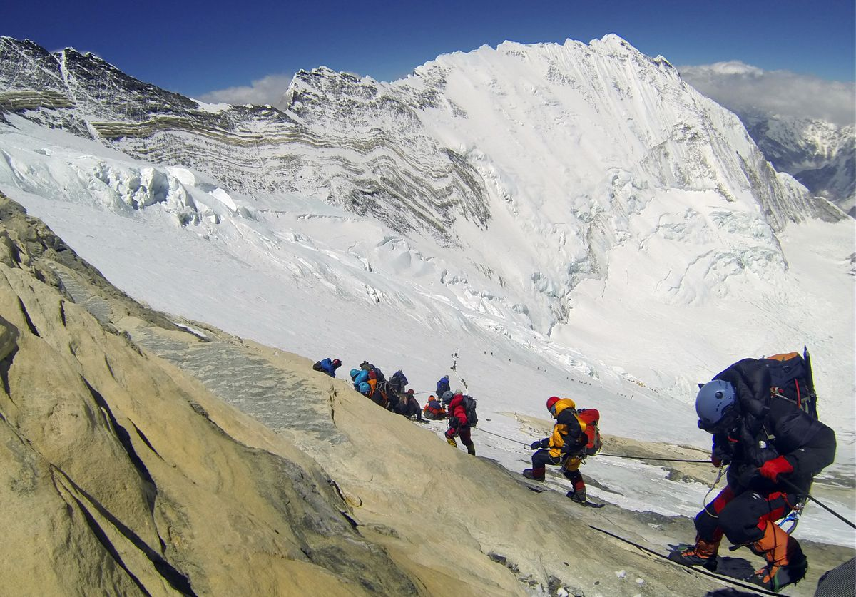 In this Saturday, May 18, 2013 photo, climbers from various countries make their way down towards Camp 4 on their way to summit the 29,035-foot Mount Everest. (AP Photo/ Pasang Geljen Sherpa)