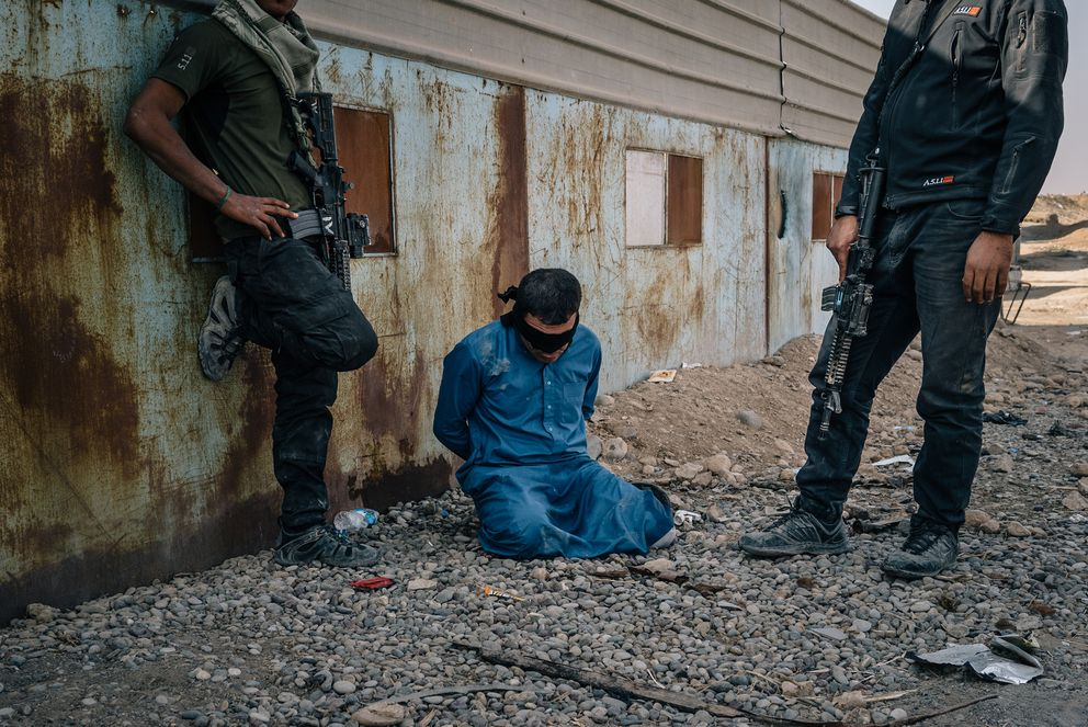 A man, blindfolded and handcuffed, kneels on the ground between two members of the Iraqi security forces after being accused of having links to the Islamic State group and being detained. (Photo for The Washington Post by Alice Martins)