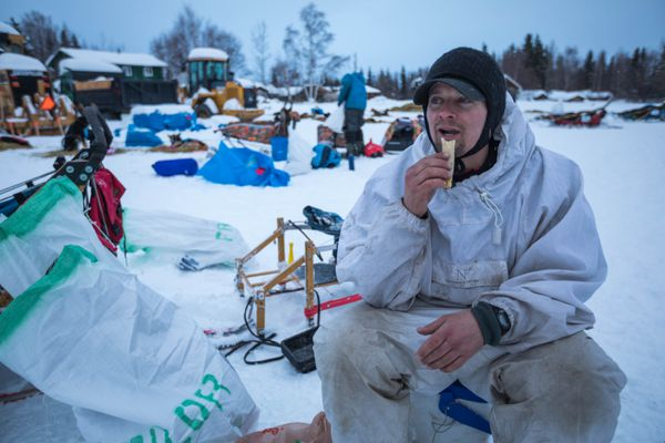 Matthew Failor eats a chicken and cheese taquito at the Nikolai checkpoint on Tuesday, March 6, 2018 during the Iditarod Trail Sled Dog Race. (Loren Holmes / ADN)