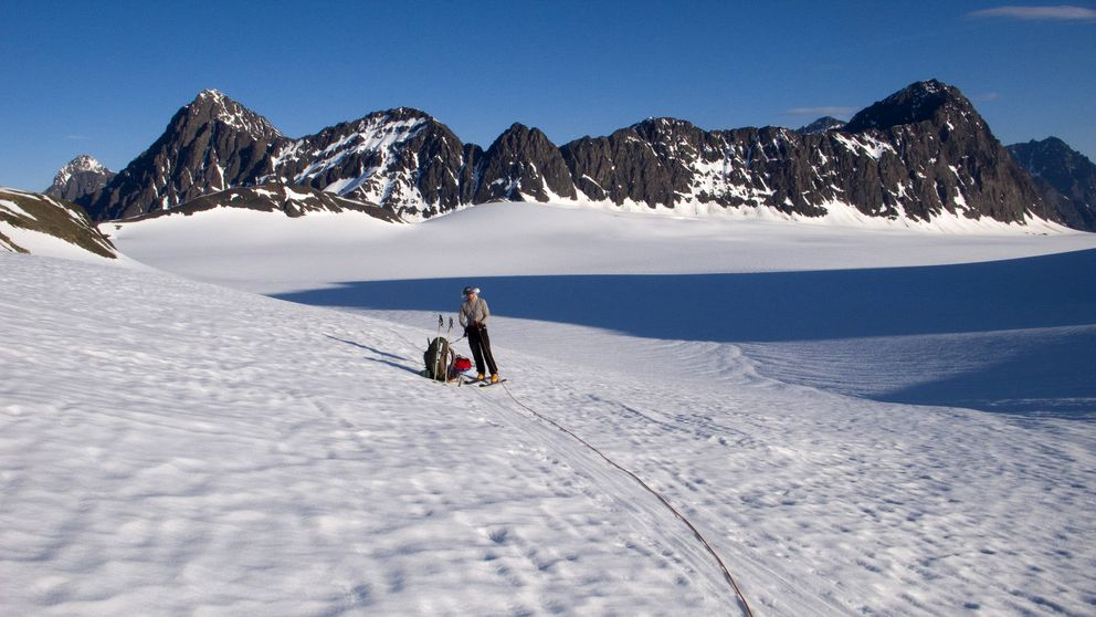 John Sykes of APU nears the top of Eklutna Glacier in 2010. The broad flat basin that makes up more than half of the glacier area is directly behind him. (Louis Sass)