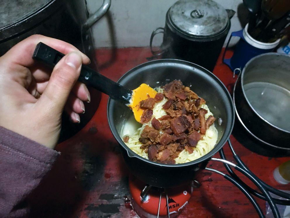 Making a backcountry version of pasta alla carbonara at Mint Hut at Hatcher Pass. (Vicky Ho / ADN)