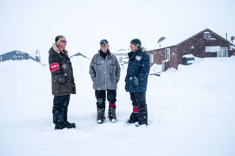 From left, veterinarians Steve Shipley, Ron Hallstrom, and Terry Hardage talk on the street in Unalakleet on Saturday during the Iditarod Trail Sled Dog Race. Shipley is from North Carolina, Hallstrom from Virginia, and Hardage from Oklahoma. (Loren Holmes / ADN)
