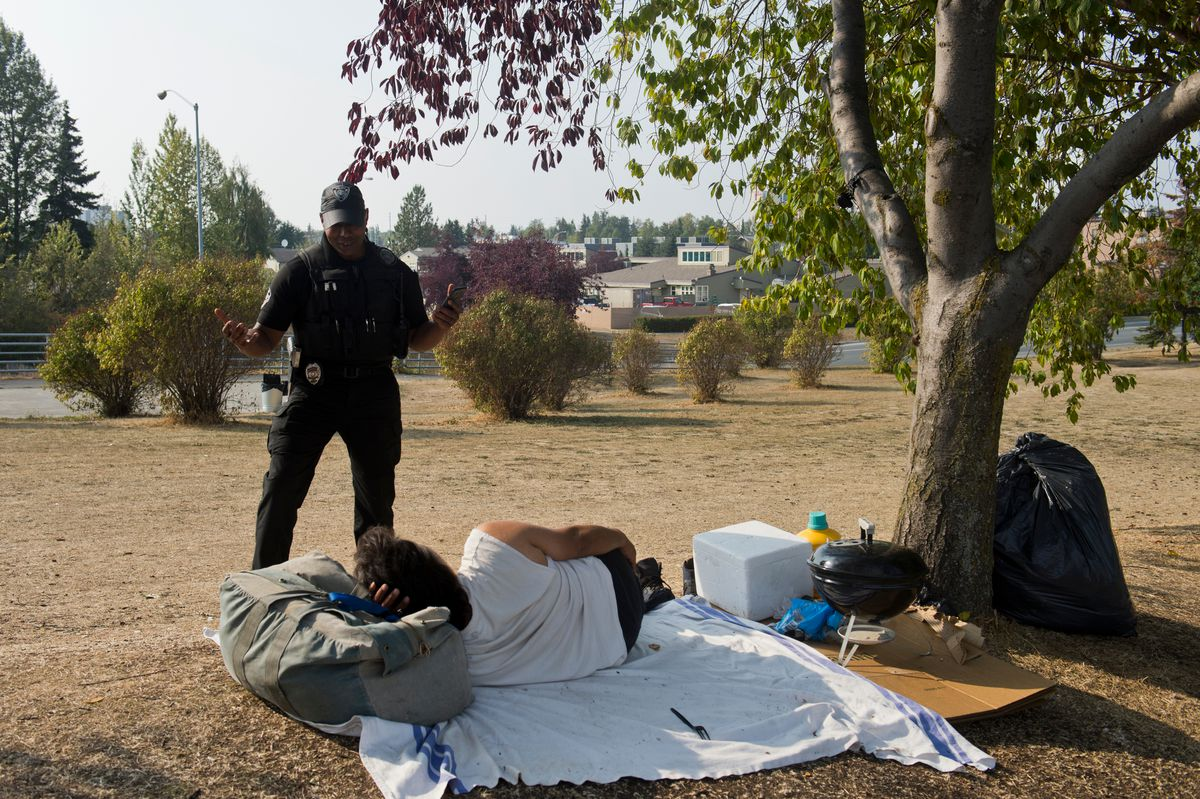 Officer Damon Jackson speaks with a man at a camp near 15th Avenue and A Street during the Point-In-Time count on August 22, 2019. (Marc Lester / ADN)