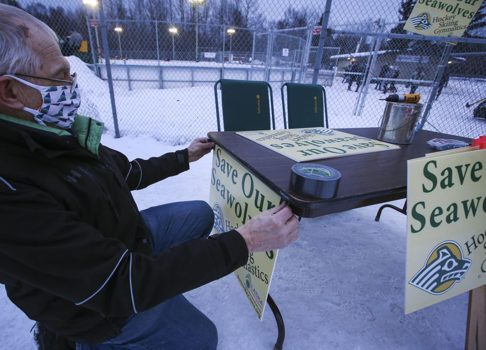 Larry Helgeson hangs up a 'Save Our Seawolves ' sign at the entrance to the Bonnie Cusack Outdoor Ice Rinks. (Emily Mesner / ADN)
