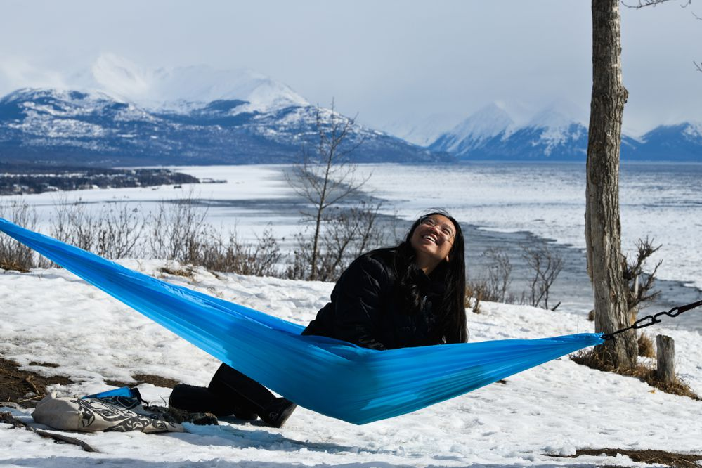 Sabrina Kessakorn looks up at a nearby bird while studying in her hammock on a bluff overlooking the Anchorage Coastal Wildlife Refuge in Kincaid Park on Wednesday, March 31, 2021. Kessakorn, a UAA student studying art and environmental science, said the spot is one of her favorite places to come to clear her head when she's feeling stressed. (Marc Lester / ADN)