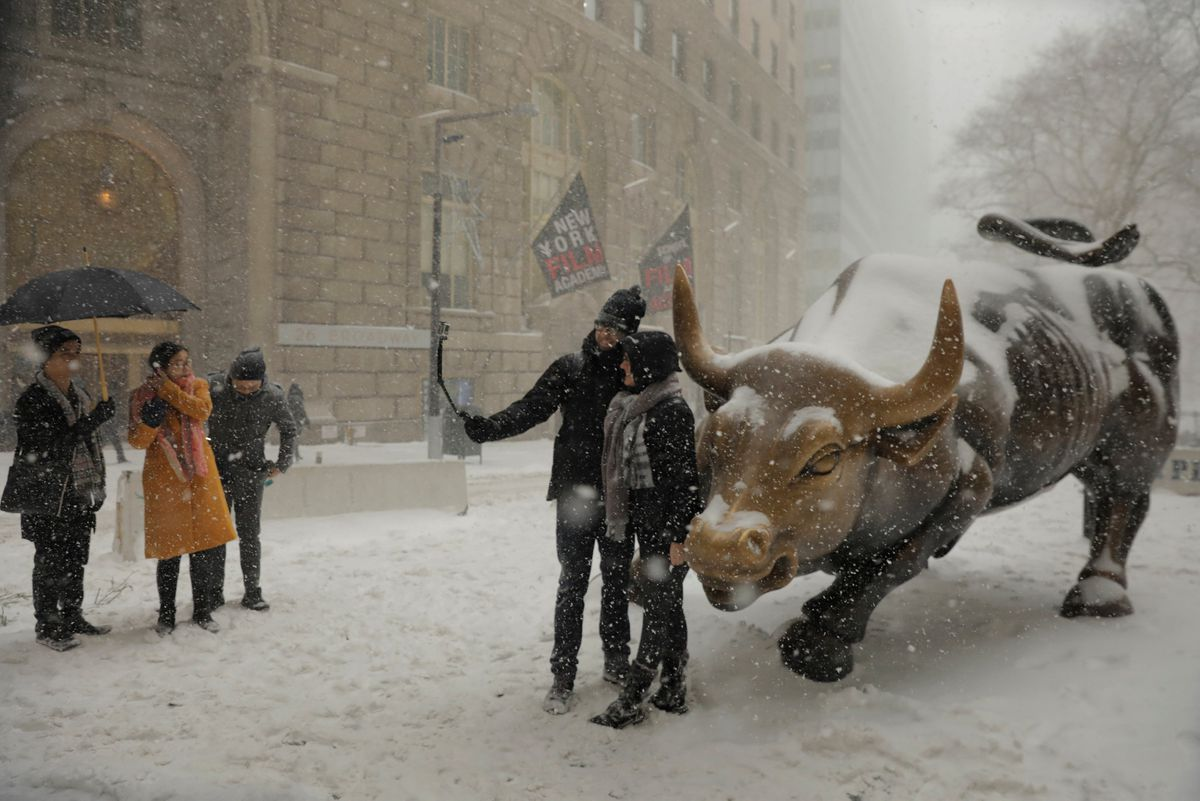 Tourists take aselfie Thursday with the Charging Bull statue during a snowstorm in New York. REUTERS/Lucas Jackson