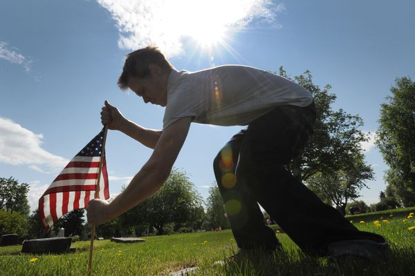 VFW Post 1685 auxiliary member Tim Felicetty places an American flags at the grave of veteran resting in the Anchorage Memorial Park Cemetery on Sunday, May 29, 2016, in preparation for Memorial Day on Monday. (Bill Roth / Alaska Dispatch News)