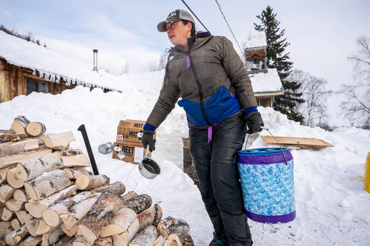 Jessie Royer makes food for her dogs in Takotna on Wednesday, March 11, 2020 during the Iditarod Trail Sled Dog Race. (Loren Holmes / ADN)