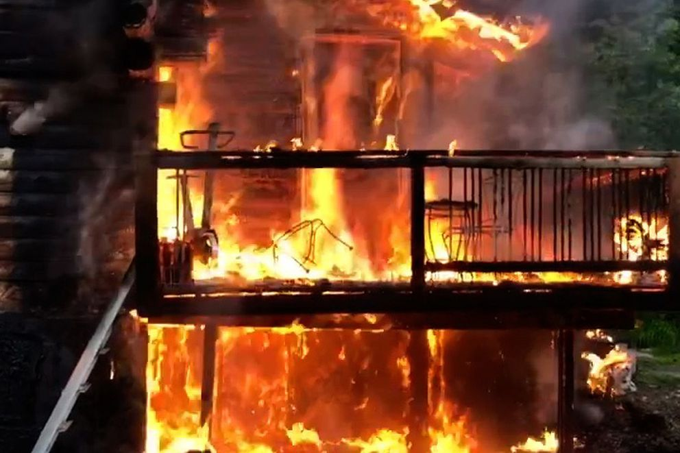 A fire near Wasilla Saturday night, June 16, 2018, destroyed a two-story log home. Three dogs died in the fire despite attempts to rescue them. (HPR Working Dogs video screenshot)