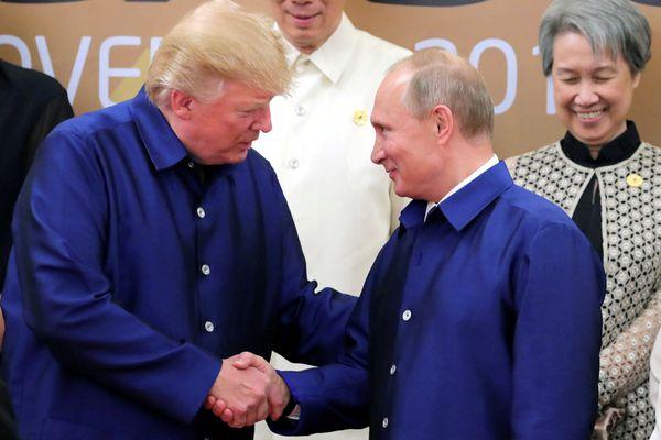 President Trump and Russian President Vladimir Putin shake hands as they take part in a family photo at the APEC summit. Sputnik/Mikhail Klimentyev/Kremlin via REUTERS