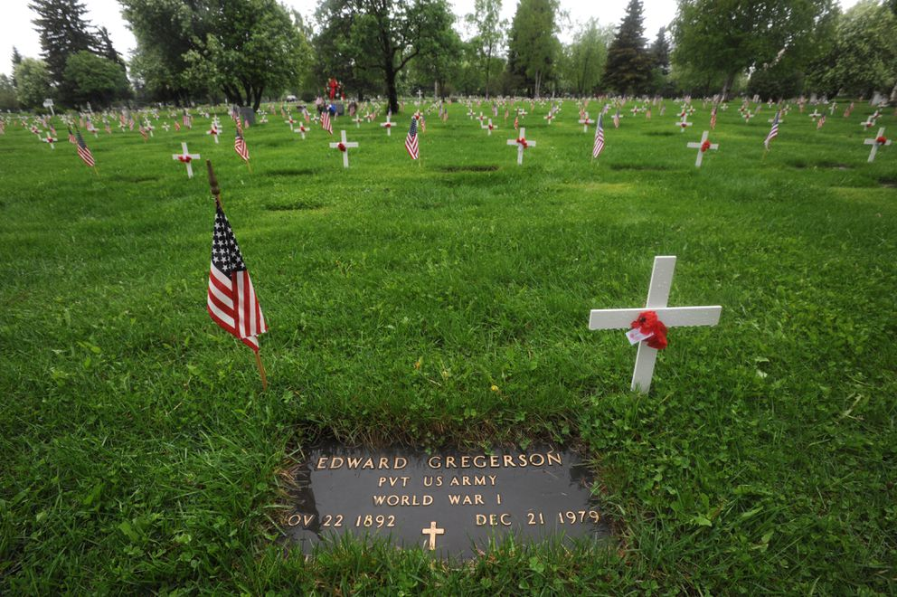An American flag and a white cross with poppies mark the grave of World War I Army veteran Edward Gregerson at the Anchorage Memorial Park Cemetery on Sunday, May 26, 2019. (Bill Roth / ADN)