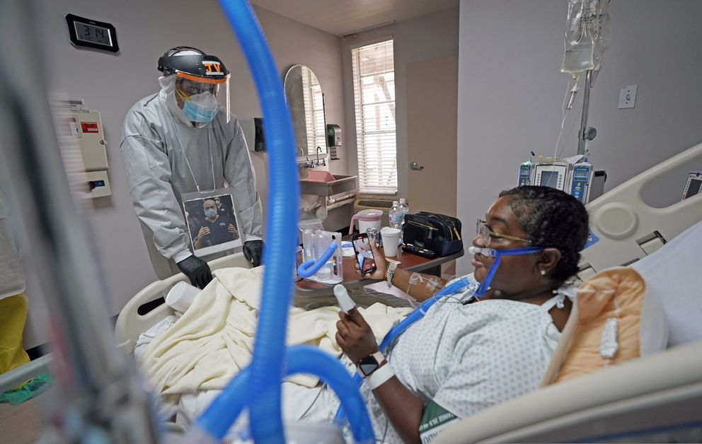 Dr. Joseph Varon, left, talks with LaTanya Robinson during rounds inside the Coronavirus Unit at United Memorial Medical Center, Monday, July 6, 2020, in Houston. Robinson says she was caring for her son when he got the virus. Both she and her husband eventually caught it. While her son and husband's symptoms were relatively mild, she went from feeling tired and struggling to move to hardly being able to breathe. (AP Photo/David J. Phillip)