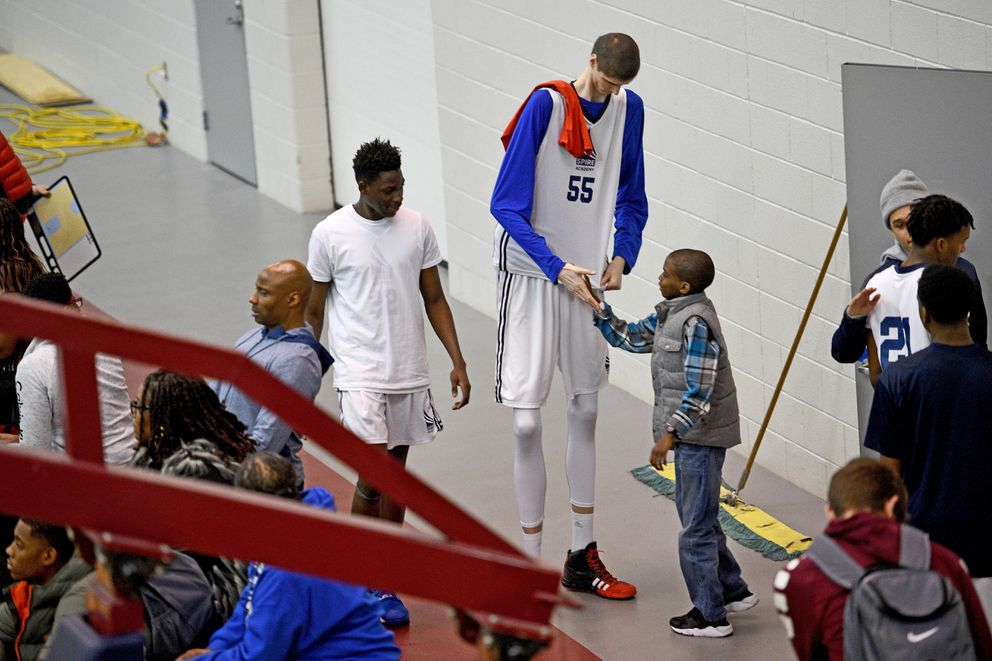 Eleven-year-old Xavier Henderson, from Columbus, Ohio, couldn't wait to meet Robert Bobroczkyi, a 7-foot-7 teen from Romania, during a tournament at SPIRE Institute in Geneva, Ohio. Washington Post photo by Katherine Frey
