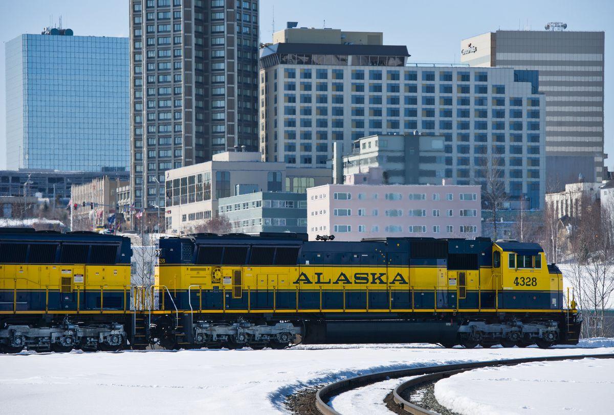An Alaska Railroad engine pulls cars through the rail yard near downtown Anchorage. (Marc Lester / ADN)