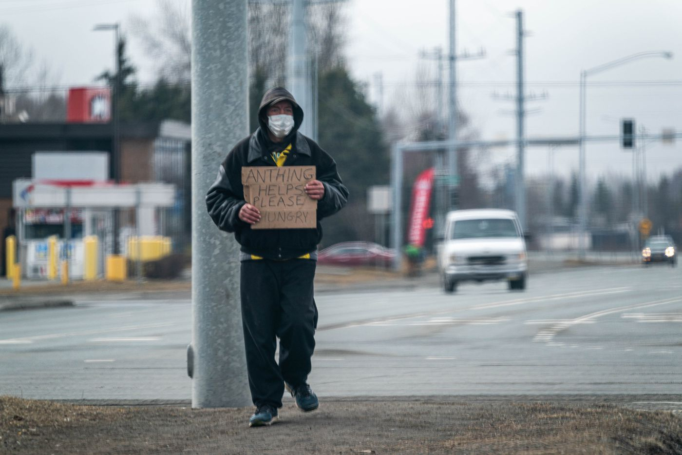 A panhandler wears a mask at an intersection in midtown Anchorage on Friday, April 17, 2020. (Loren Holmes / ADN)