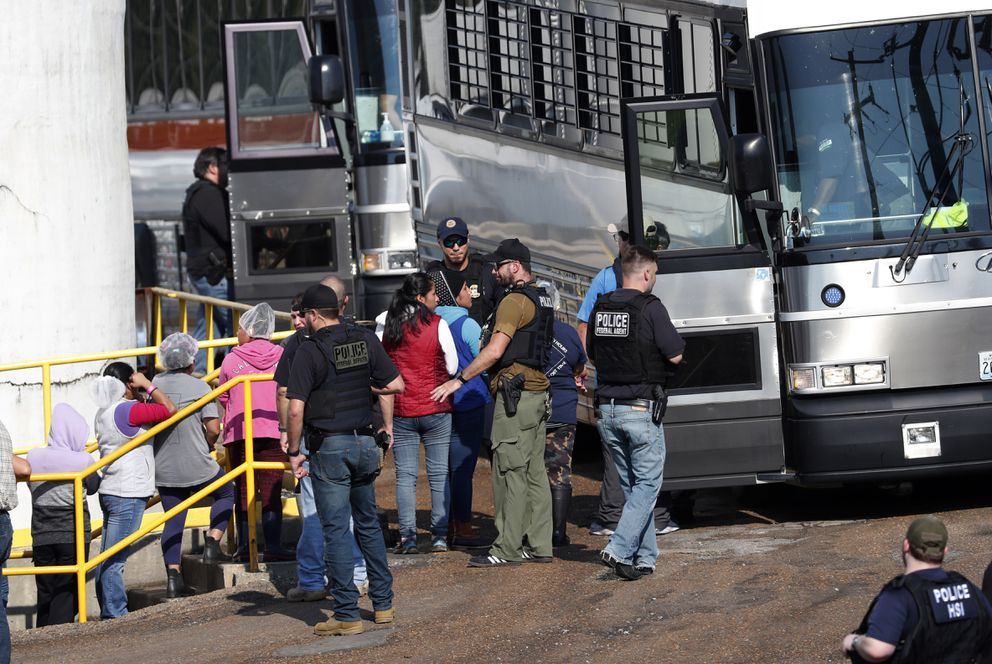 Handcuffed female workers are escorted into a bus for transportation to a processing center following a raid by U.S. immigration officials at a Koch Foods Inc., plant in Morton, Miss., Wednesday, Aug. 7, 2019. U.S. immigration officials raided several Mississippi food processing plants on Wednesday and signaled that the early-morning strikes were part of a large-scale operation targeting owners as well as employees. (AP Photo/Rogelio V. Solis)