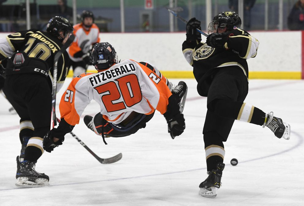 South's Logan Maddox, left, looks for the puck as Aiden Fitzgerald of West and Reed Donald of South head for the ice after a collision. (Photo by Bob Hallinen)