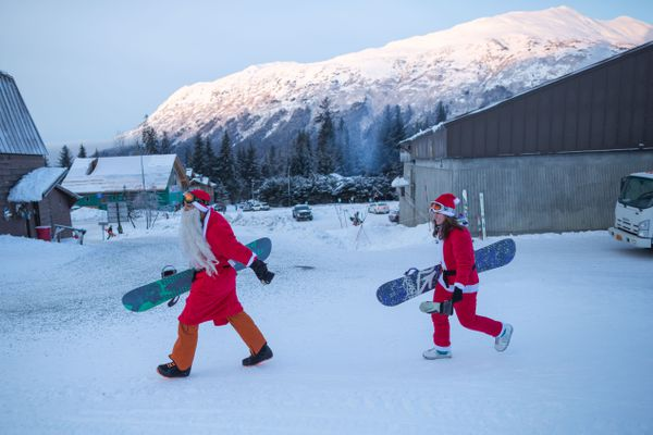 LOREN HOLMES / Alaska Dispatch News Eric Ward, left, and Jessie Pooler make their way to the chairlift at Alyeska Resort on Dec. 24, 2015. The resort traditionally offers free Christmas Eve lift tickets to skiers and snowboarders dressed in Santa outfits, a perk over 600 people took advantage of this year.
