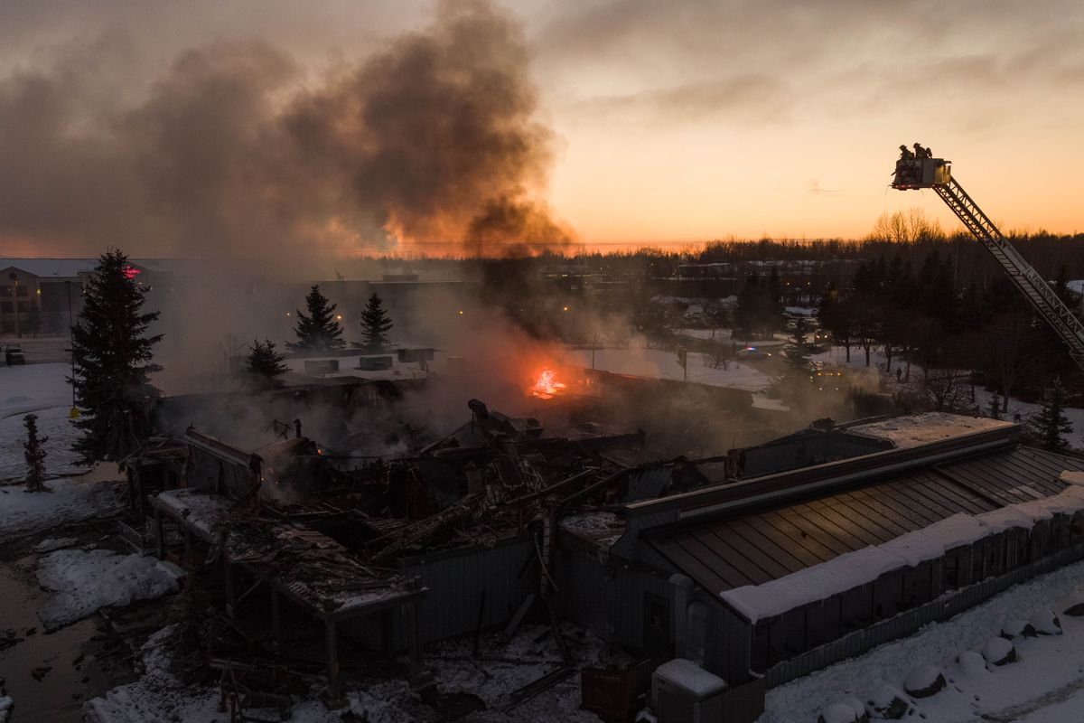 Anchorage firefighters Jeremiah Moss, left, and Will Anderstrom monitor a fire at the former Sea Galley on Thursday, Jan. 3, 2019. The fire was burning beneath a collapsed part of the roof and the firefighters were waiting for the fire to burn a hole through the roof so they could use water to put it out. (Loren Holmes / ADN)