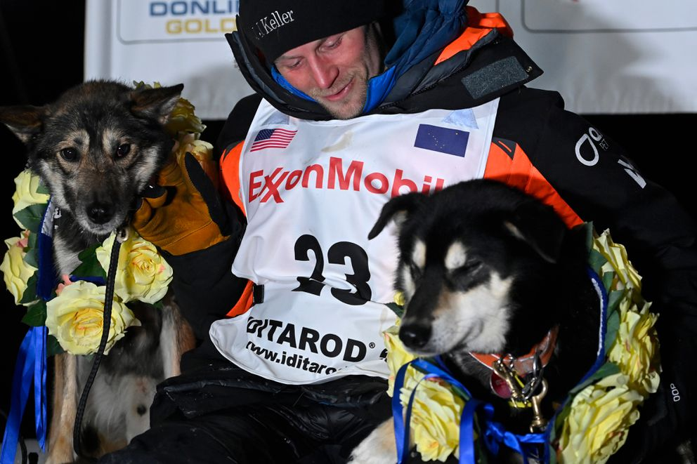 Dallas Seavey poses with lead dogs North, left, and Gamble after winning a record-tying fifth Iditarod title. (Marc Lester / ADN)